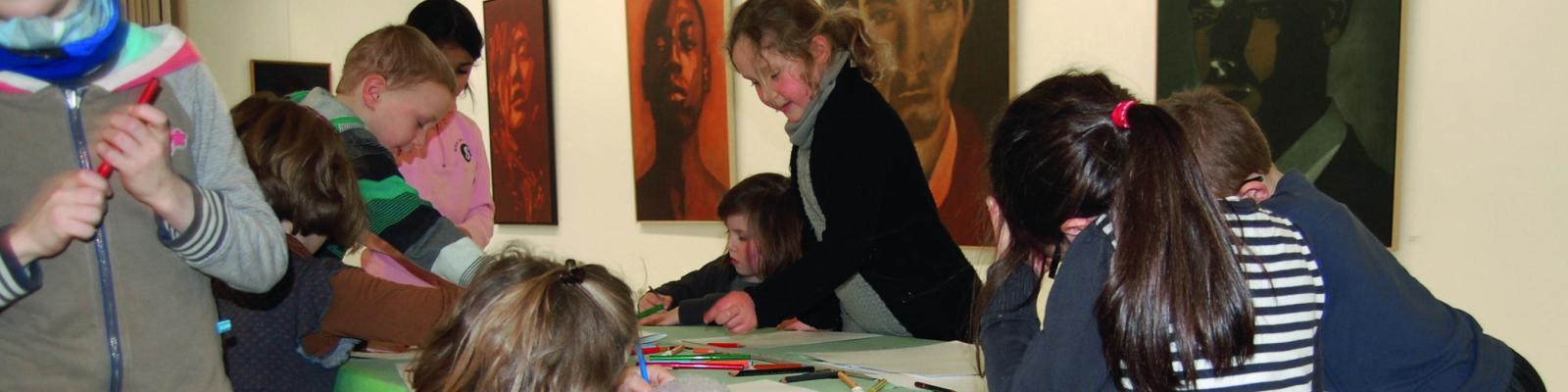 Kinderen die in de Bijl aan het tekenen zijn. Op de achtergrond hangen er schilderijen.