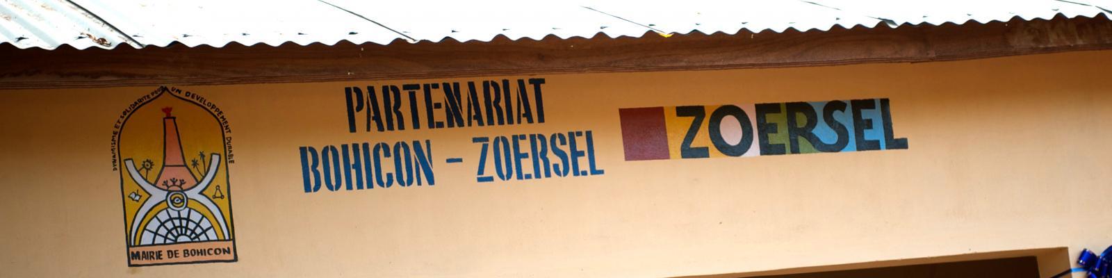 luifel in Bohicon waar de gemeentelogo's van Zoersel en Bohicon naast elkaar staan