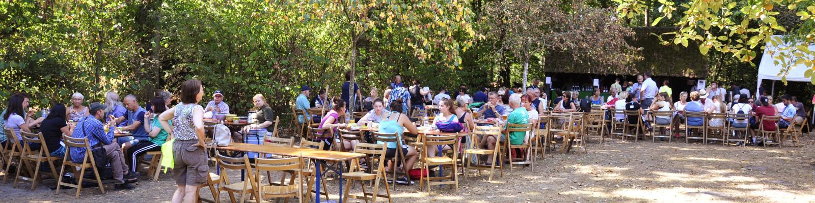 Mensen zitten buiten aan tafel op een evenement en drinken iets.