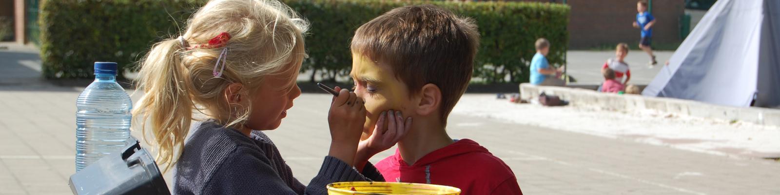 twee kinderen schminken elkaar