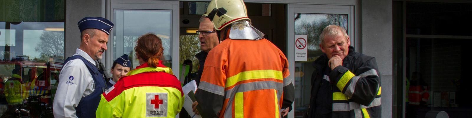 een politieman, een brandweerman en iemand van het Rode Kruis in overleg bij een rampenoefening