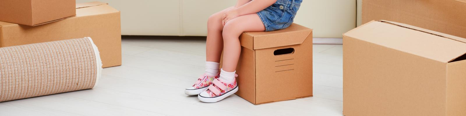 klein meisje zit op verhuisdoos