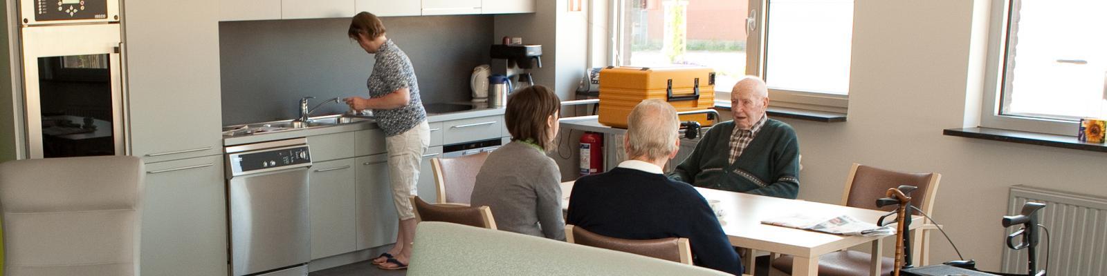 ouderen die gezellig tafelen in de keuken van het woonzorgcentrum