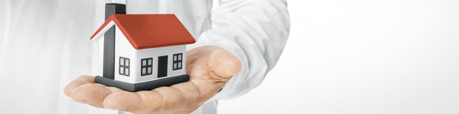 banner man houdt klein huis in zijn hand