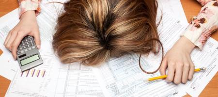 wanhopige vrouw met rekenmachine boven facturen