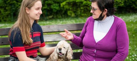 jongere vrouw met hond doet een babbeltje met een oudere vrouw op een bank in het park
