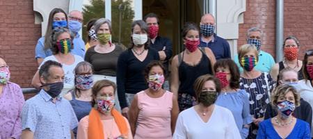 groepsfoto van bezielers en medewerkers van Mondmaskerszoersel en burgemeester met een mondmasker