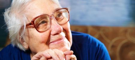 oudere vrouw zit in haar zetel en kijkt gelukkig voor zich uit