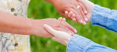 jongere vrouw helpt oudere vrouw en houdt haar handen vast
