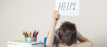 jongen ligt met hoofd in de boeken en steekt een blaadje papier omhoog waarom 'HELP!' staat