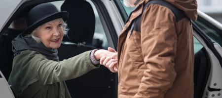 man helpt vrouw uit de auto