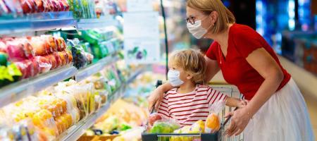 mama en kind in de supermarkt met een mondmasker