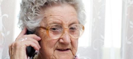 oude dame met bril aan de telefoon
