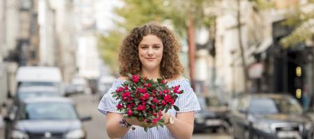 jonge vrouw pronkt met azalea in de hand in de stad