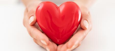 vrouw houdt een rood hart in haar handen