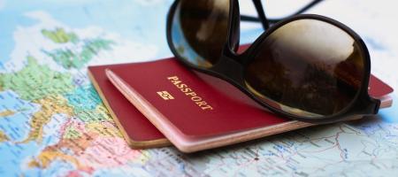 zonnebril en paspoort ligt klaar op kaart