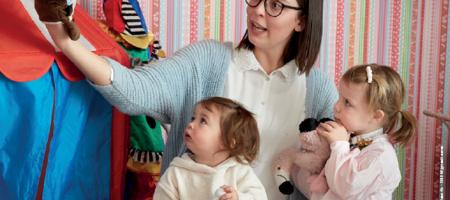 onthaalouder speelt poppenkast met twee kleine kinderen