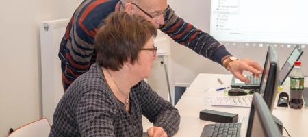 oudere man helpt oudere vrouw met computerproblemen