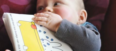 baby houdt plastic boekje vast