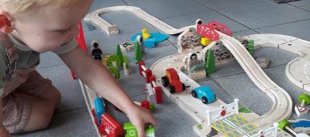 kleine jongen speelt enthousiast met treinset
