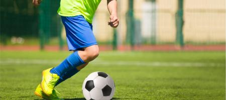jongen speelt voetbal op voetbalveld