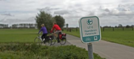 close-up van een knooppunt bewegwijzering met twee fietsers op de achtergrond