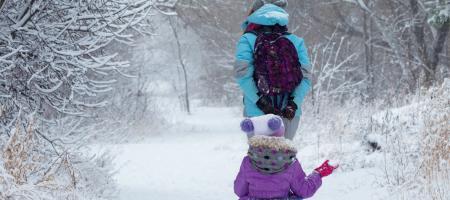 ouder neemt kind mee op sleeptouw in de sneeuw