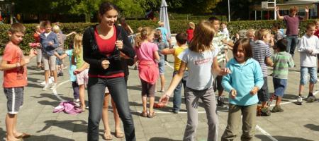 kinderen en monitoren dansen op het speelplein
