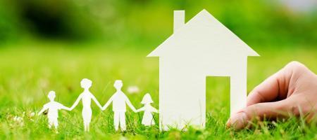 houten huisje in het gras met een gezin
