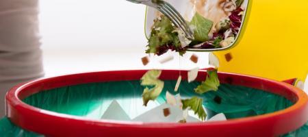 vrouw doet bruikbare etensresten in de vuilbak