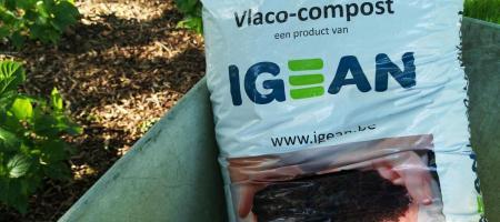 een zak vlaco-compost ligt in een kruiwagen