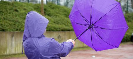 vrouw met wegwaaiende paraplu in storm