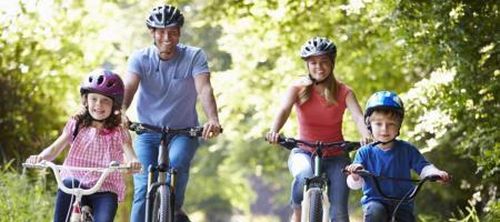 gezin met twee kleine kinderen fietst al lachend