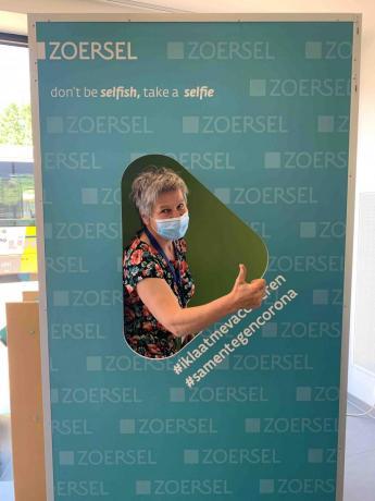 bibliotheekmedewerker neemt een selfie in de gloednieuwe fotobooth
