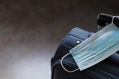 reiskoffer staat klaar. Mondmasker hangt aan de reiskoffer.
