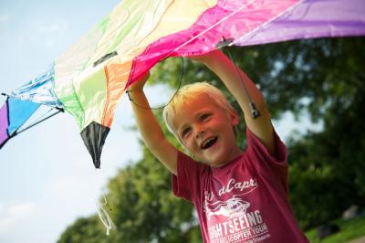 jongen houdt kleurrijke vlieger in de lucht