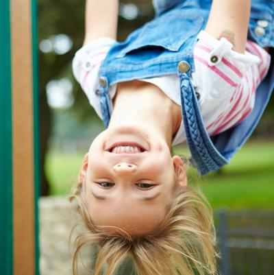 klein blond meisje hangt al lachend ondersteboven aan een speeltuig