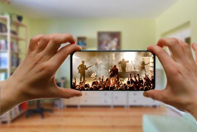 vrouw bekijkt concert in de woonkamer op haar smartphone