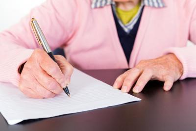 oudere vrouw schrijft brief met vulpen