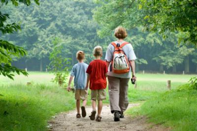 mama wandelt met twee kinderen in het bos