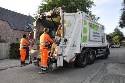 twee afvalophalers staan achteraan op een vuilniswagen