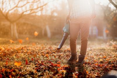 man blaast de blaadjes van de bomen in zijn tuin weg met een bladblazer