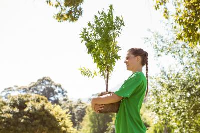 een jonge vrouw loopt glimlachend rond met een jonge boom om te planten
