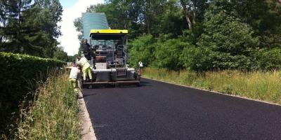 mannen aan het werk om nieuwe asfalt aan te leggen