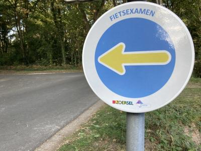 bordje met pijl naar links wijst de richting van het fietsexamen aan