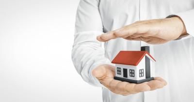 man houdt hand boven een klein huis