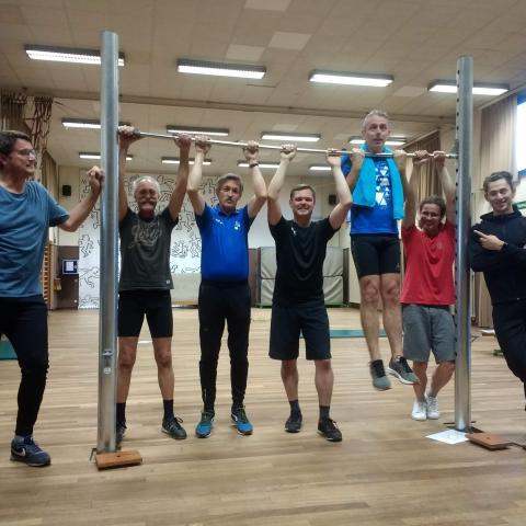 Groep van 6 sportende heren en de trainer