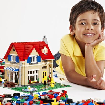 jongen naast huis gemaakt uit Lego